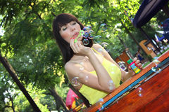 Sweet girl blowing bubbles outdoor Stock Photos