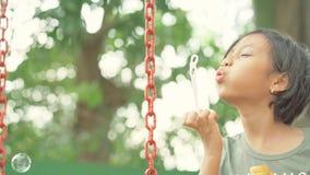 Sweet girl blowing soap bubbles on the swing