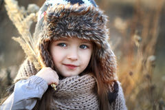 Sweet girl in a cap with the deer in autumn in a field of dry grass Stock Photos