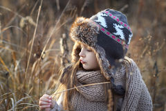 Sweet girl in a cap with the deer in autumn in a field of dry grass Royalty Free Stock Photo