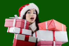 Sweet girl in christmas hat and holds presents Royalty Free Stock Images