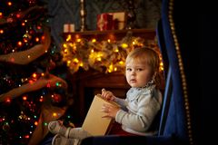 Sweet girl in Christmas tree. The child is sitting in a blue armchair with Christmas presents Stock Photo