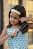Sweet Girl Combing her hair Royalty Free Stock Image