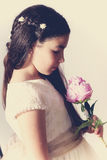 Sweet girl with communion dress holding a peony Royalty Free Stock Photography