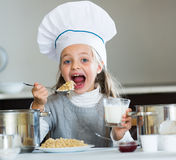 Sweet girl in cook hat eating kasha in kitchen Royalty Free Stock Photos