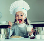 Sweet girl in cook hat eating kasha in kitchen Royalty Free Stock Image