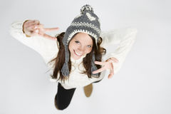 Sweet girl in cool winter clothing laughing, making victory sign Stock Image