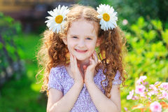 Sweet girl with daisies in her hair ponytail. Royalty Free Stock Photos