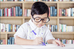 Sweet girl drawing on a paper in library Stock Images