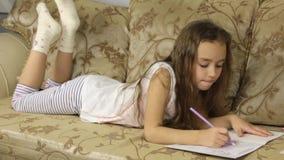 Sweet girl draws lying on the sofa stock video