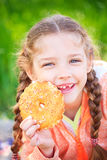 Sweet girl with a fallen tooth holding cookies in her hand Royalty Free Stock Photography
