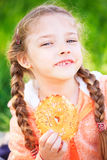 Sweet girl with a fallen tooth holding a cookies  in her hand. Sweet girl with a fallen tooth holding a cookies in her hand on nature Royalty Free Stock Photo