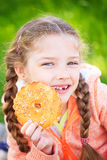 Sweet girl with a fallen tooth holding cookies in her hand Royalty Free Stock Image