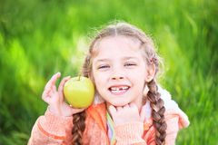 Sweet girl with a fallen toth holding an apple in her hand Stock Photos