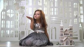 A sweet girl in a gray shiny dress sits near a toy palace and sends an air kiss, a greeting card. Slow motion shooting stock footage