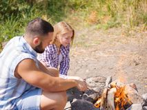 A loving couple bred a fire on a picnic in the forest to fry meat. A girl is kindling a fire in nature. Summer time. A sweet girl helps her boyfriend to kindle a Royalty Free Stock Images