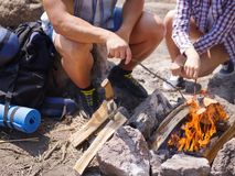 A loving couple bred a fire on a picnic in the forest to fry meat. A girl is kindling a fire in nature. Summer time Royalty Free Stock Photos