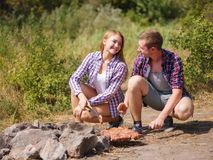 A loving couple bred a fire on a picnic in the forest to fry meat. A girl is kindling a fire in nature. Summer time Stock Photo