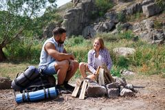 A loving couple bred a fire on a picnic in the forest to fry meat. A girl is kindling a fire in nature. Summer time. A sweet girl helps her boyfriend to kindle a Royalty Free Stock Image
