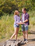 A loving couple bred a fire on a picnic in the forest to fry meat. A girl is kindling a fire in nature. Summer time. A sweet girl helps her boyfriend to kindle a Stock Photo
