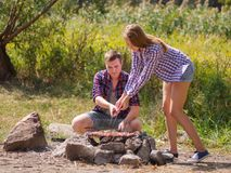 A loving couple bred a fire on a picnic in the forest to fry meat. A girl is kindling a fire in nature. Summer time. A sweet girl helps her boyfriend to kindle a Stock Photos
