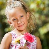 Sweet girl holding flowers outdoors. Royalty Free Stock Photo