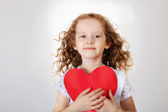 Sweet girl holding red paper heart. Stock Photo