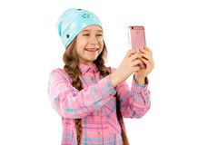 A sweet girl holds a smart phone in her hands and smiles. Isolated on a white background. Royalty Free Stock Image