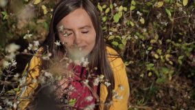 Sweet girl inhales the scent of a blooming tree on a warm spring day. A sweet girl inhales the scent of a blooming tree on a warm spring day stock video footage