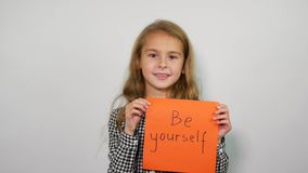 Sweet girl with inspirational slogan in hands. Be yourself.  stock video footage