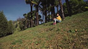 Sweet girl in jeans and jacket is sitting on a green lawn under palm trees. A sweet girl in jeans and jacket is sitting on a green lawn under palm trees stock video footage