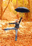 Sweet girl jumping with umbrella Stock Images