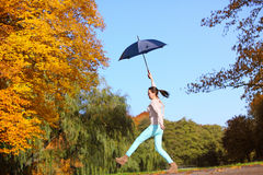Sweet girl jumping with umbrella in autumnal park Stock Photo