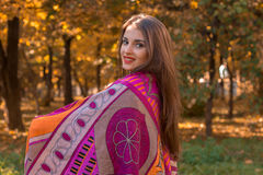 Sweet girl keeps the big pink scarf on the shoulders and smiles Royalty Free Stock Photo