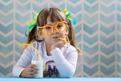 Sweet girl kid drinking milk with funny glasses straw. royalty free stock photos