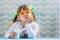 Sweet girl kid drinking milk with funny glasses straw. stock photo