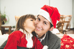 Sweet girl kissing dad for Christmas Royalty Free Stock Photography
