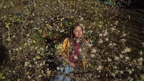 Sweet girl lays down under a flowering tree and enjoys the scent and sunshine. A sweet girl lays down under a flowering tree and enjoys the scent and sunshine stock video