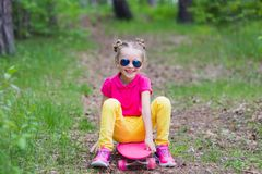 Sweet girl learns to ride a skateboard in the park in the summer. Sweet girl learns to ride a skateboard in the park stock images