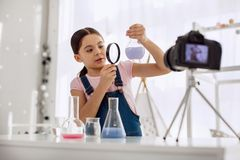 Sweet girl looking at chemical flask through magnifying glass Royalty Free Stock Image