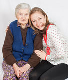 The sweet girl and the old woman. Old woman and the sweet young girl Stock Photos