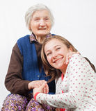 The sweet girl and the old woman staying together. Old woman and the sweet young girl Stock Photos