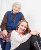 The sweet girl and the old woman staying together. Old woman and the sweet young girl Royalty Free Stock Photography