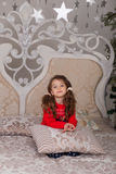 Sweet girl in pajamas getting ready for bed. The child indulges in bed before going to sleep Royalty Free Stock Photos