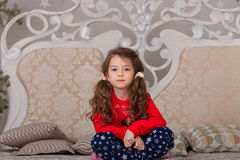Sweet girl in pajamas getting ready for bed. The child indulges in bed before going to sleep Stock Photo