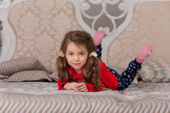 Sweet girl in pajamas getting ready for bed. The child indulges in bed before going to sleep Royalty Free Stock Image