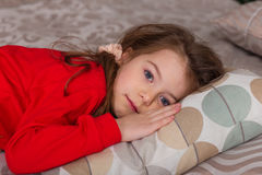 Sweet girl in pajamas getting ready for bed. The child indulges in bed before going to sleep Stock Images