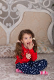 Sweet girl in pajamas getting ready for bed. The child indulges in bed before going to sleep Royalty Free Stock Images