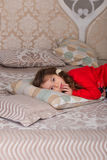 Sweet girl in pajamas getting ready for bed. The child indulges in bed before going to sleep Stock Photos