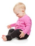 Sweet girl in pink jacket and black trousers sits Royalty Free Stock Images